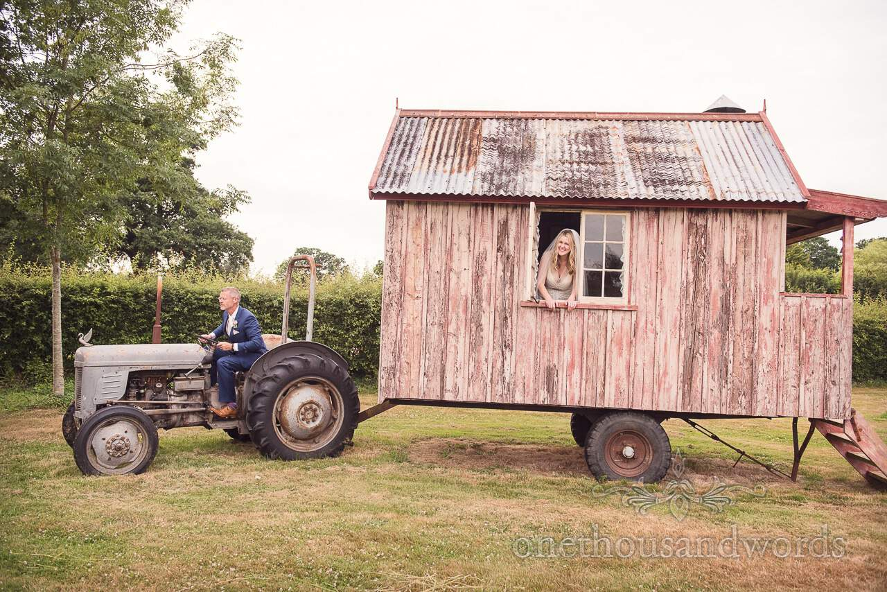 Bride and groom pose for wooden caravan picture from Countryside Manor House Wedding