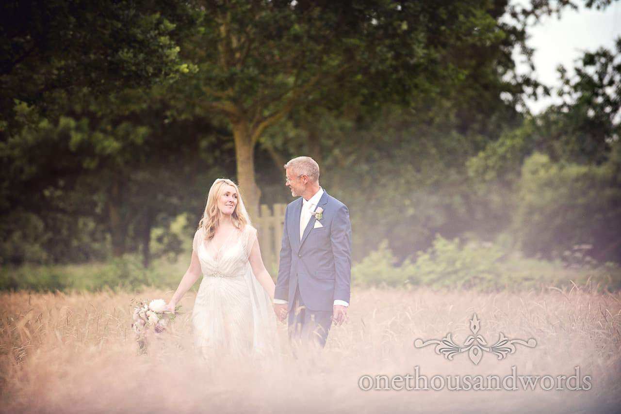 Bride and groom walk hand in hand at Countryside Manor House Wedding