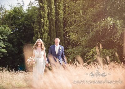 Bride and groom walking hand in hand at Countryside Manor House Wedding