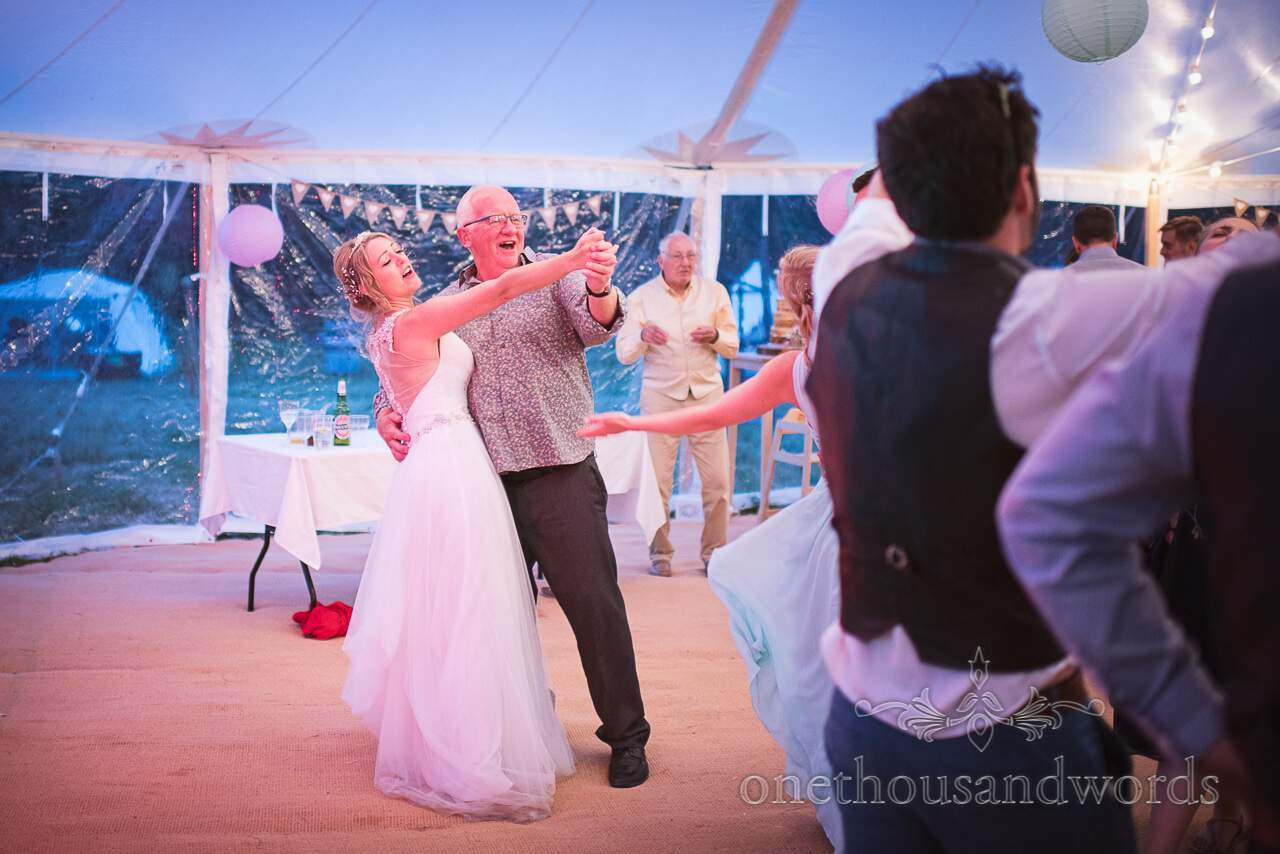 Bride dances with guest at Purbeck Valley Farm Wedding Photographs