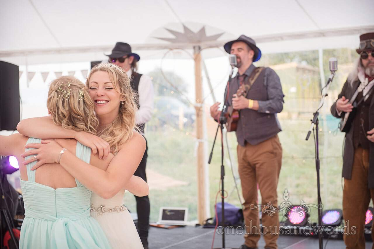 Bride embraces bridesmaid on dance floor at Purbeck Valley Farm Wedding Photographs