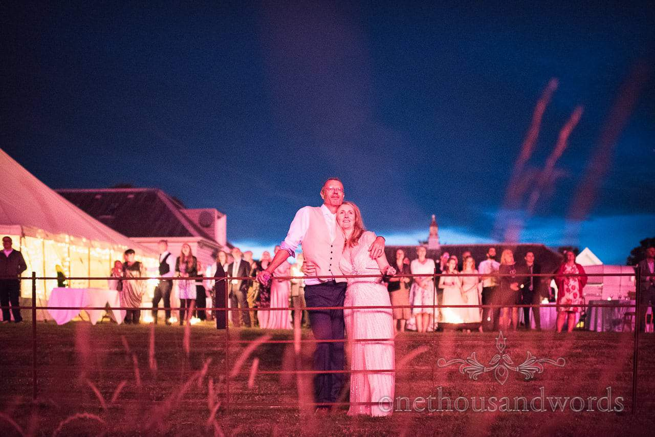 Bride , groom and guests watch fireworks on lawn at Countryside Manor House Wedding