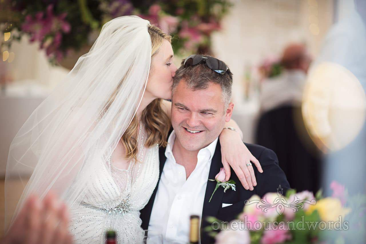 Bride kisses a groomsman during marquee reception at countryside wedding
