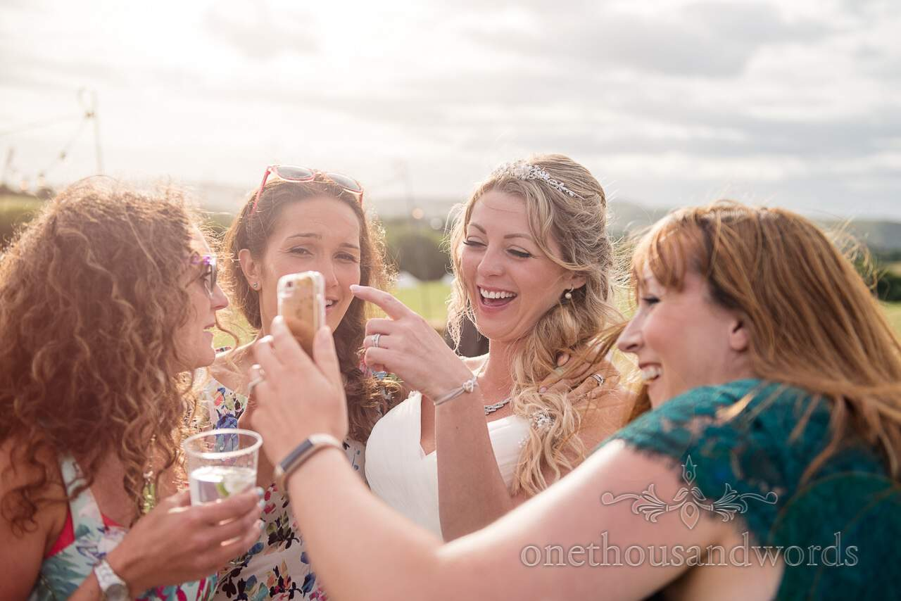 Bride looks at phone camera with friends at Purbeck Valley Farm Wedding Photographs