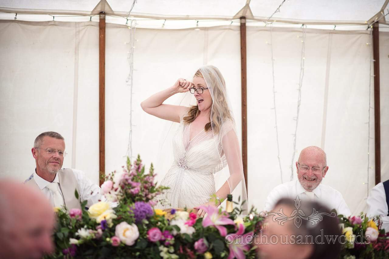 Bride puts on glasses so that she can read speech from countryside wedding