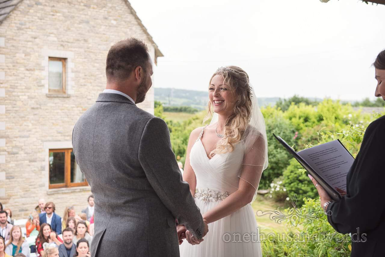 Bride smiles at her husband to be from Purbeck Valley Farm Wedding Photographs