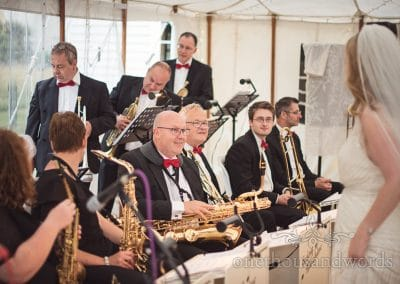Bride talks to swing band during reception at countryside wedding