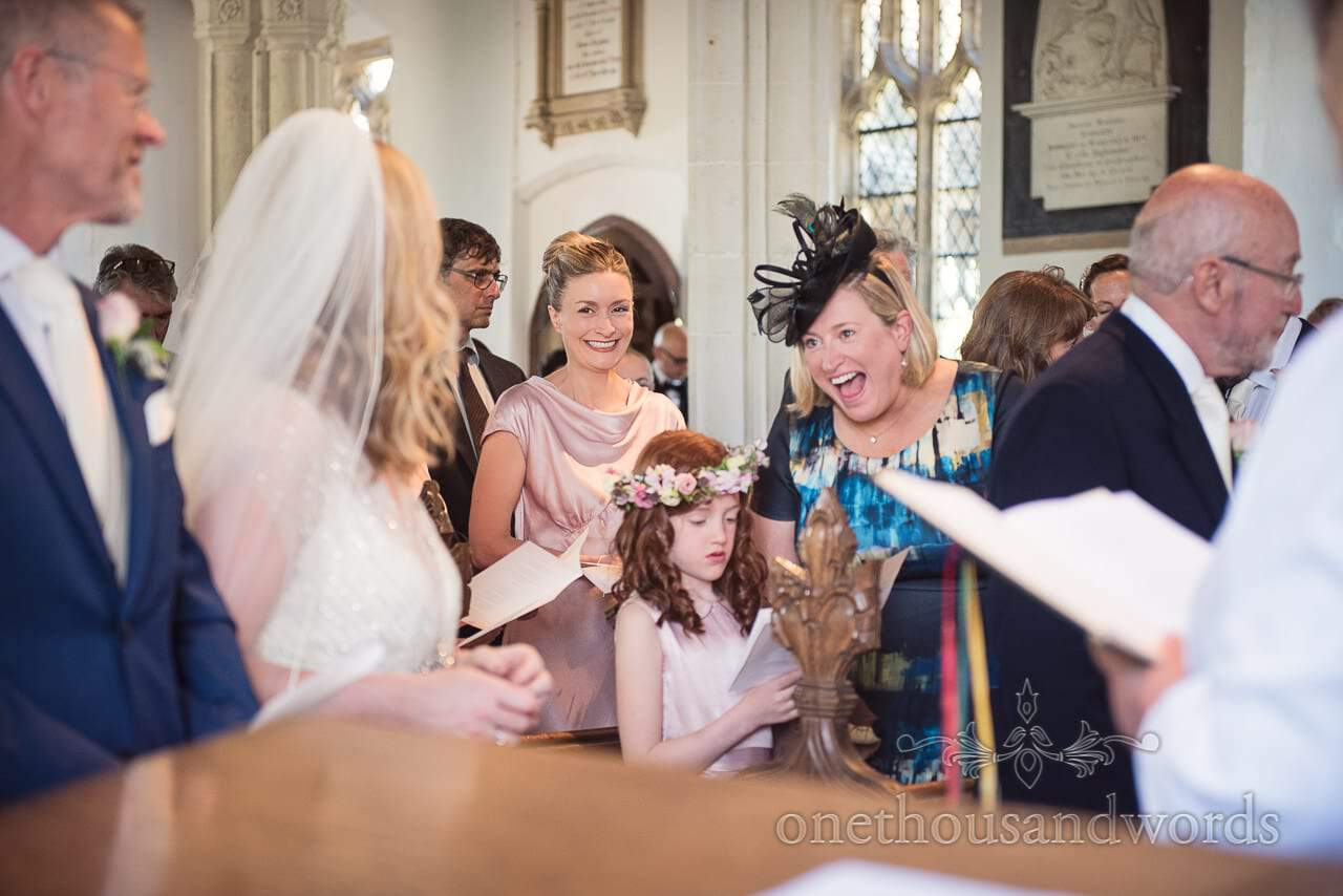 Bridesmaid and guest react to bride in church countryside wedding