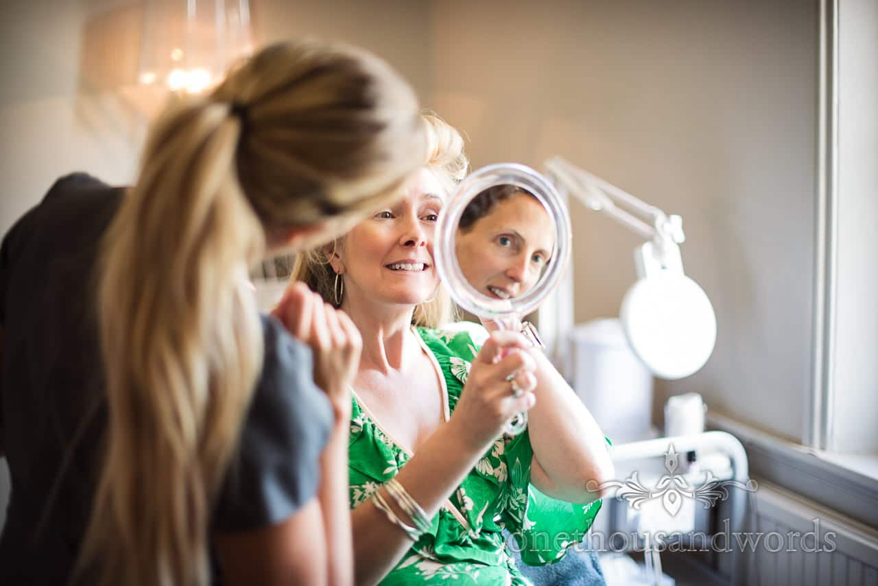 Bridesmaids face in mirror as bride has hair styled for Countryside Manor House Wedding