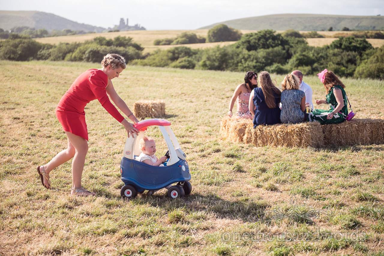 Countryside wedding guests relaxing in field with Corfe Castle in background