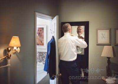 Groom does tie in mirror while groomsman shaves in bathroom