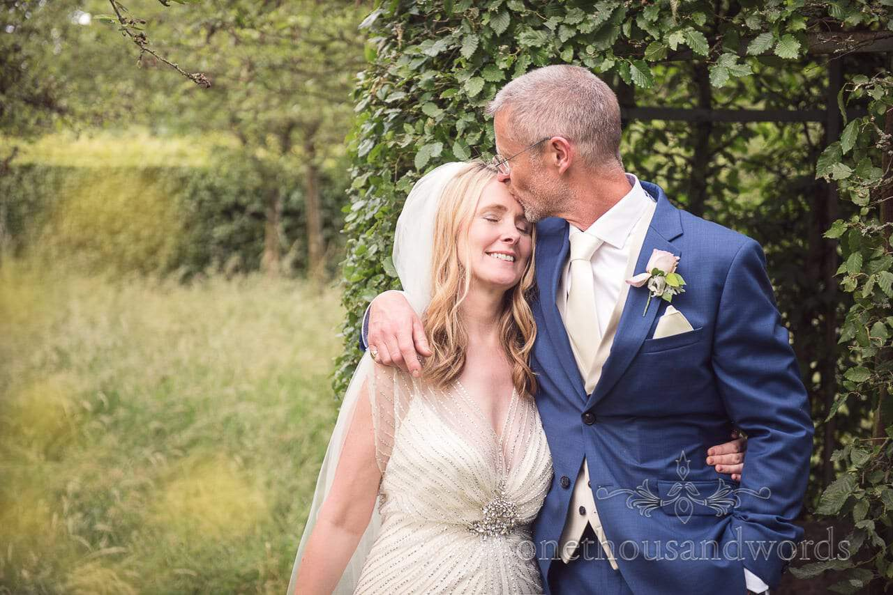 Groom kisses his bride on the head at Countryside Manor House Wedding