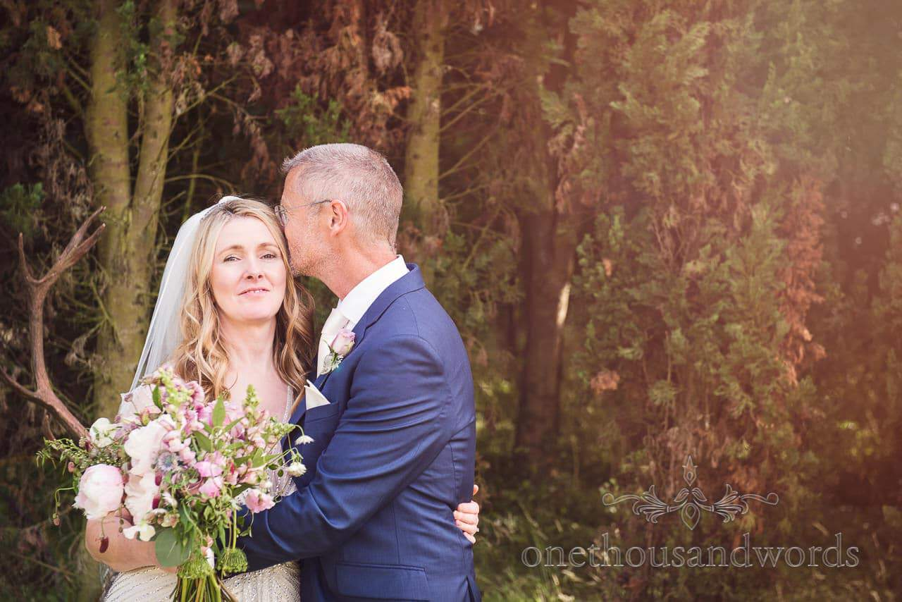 Groom kisses his bride on the head from countryside wedding