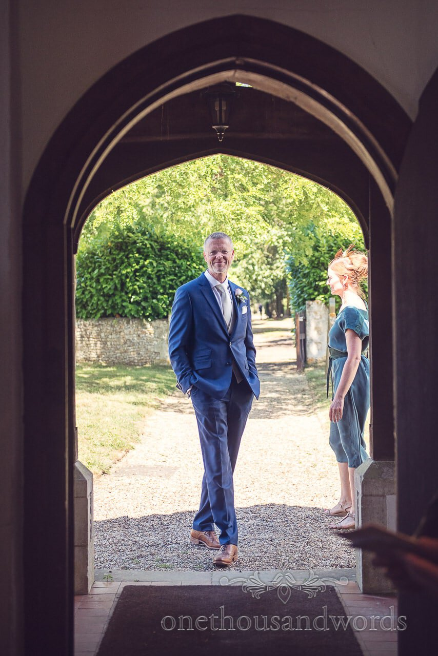 Groom outside church doorway from Countryside Manor House Wedding