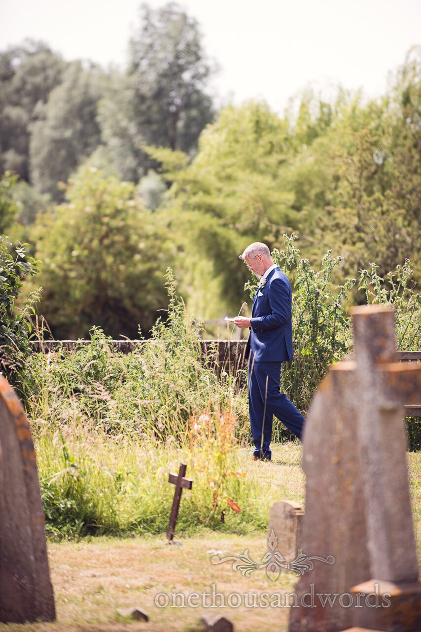 Groom takes a moment in church yard from Countryside Wedding