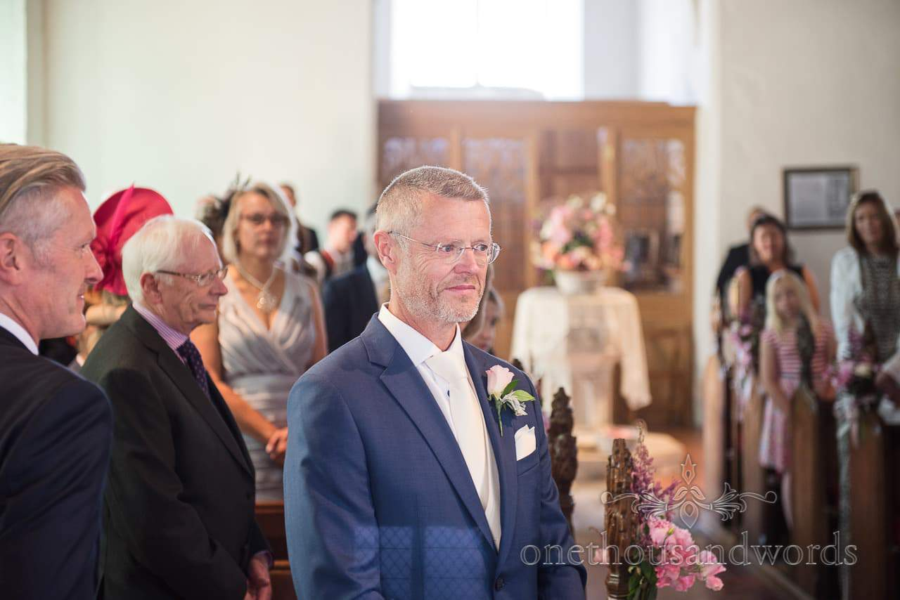 Groom waiting in church for bridal party to arrive from Countryside Manor House Wedding