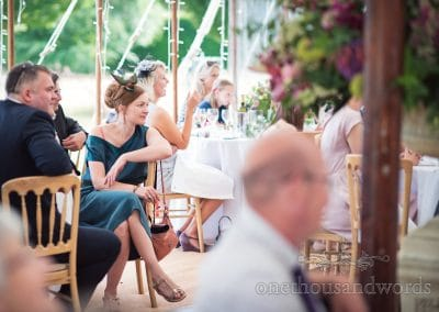 Guest looks on as top table speeches are delivered at countryside wedding