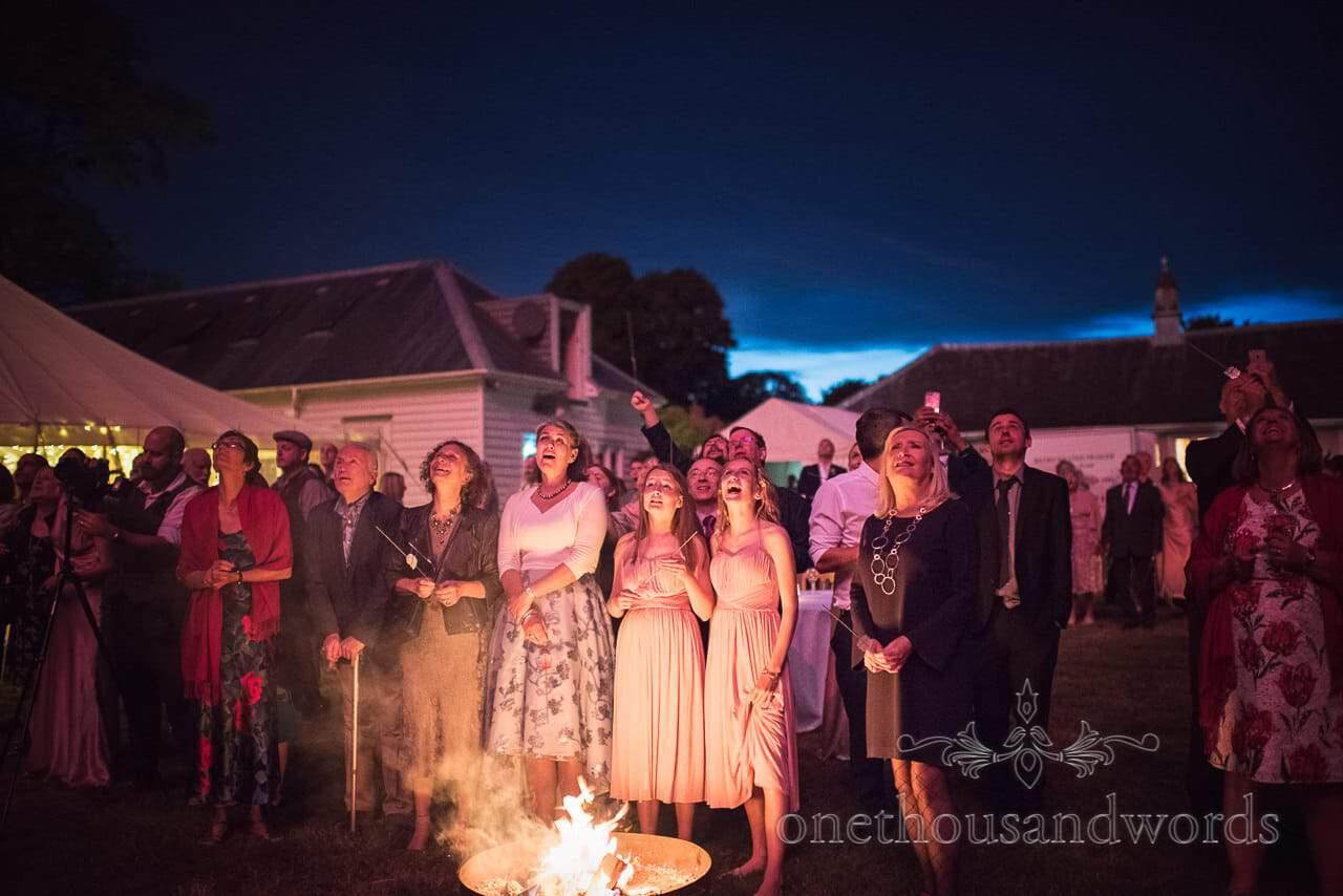 Guests around fire pit enjoy fireworks display at Countryside Manor House Wedding