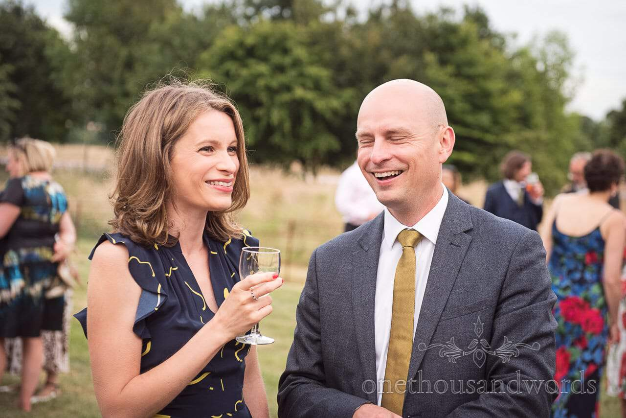 Guests enjoy a drink and a laugh during countryside wedding