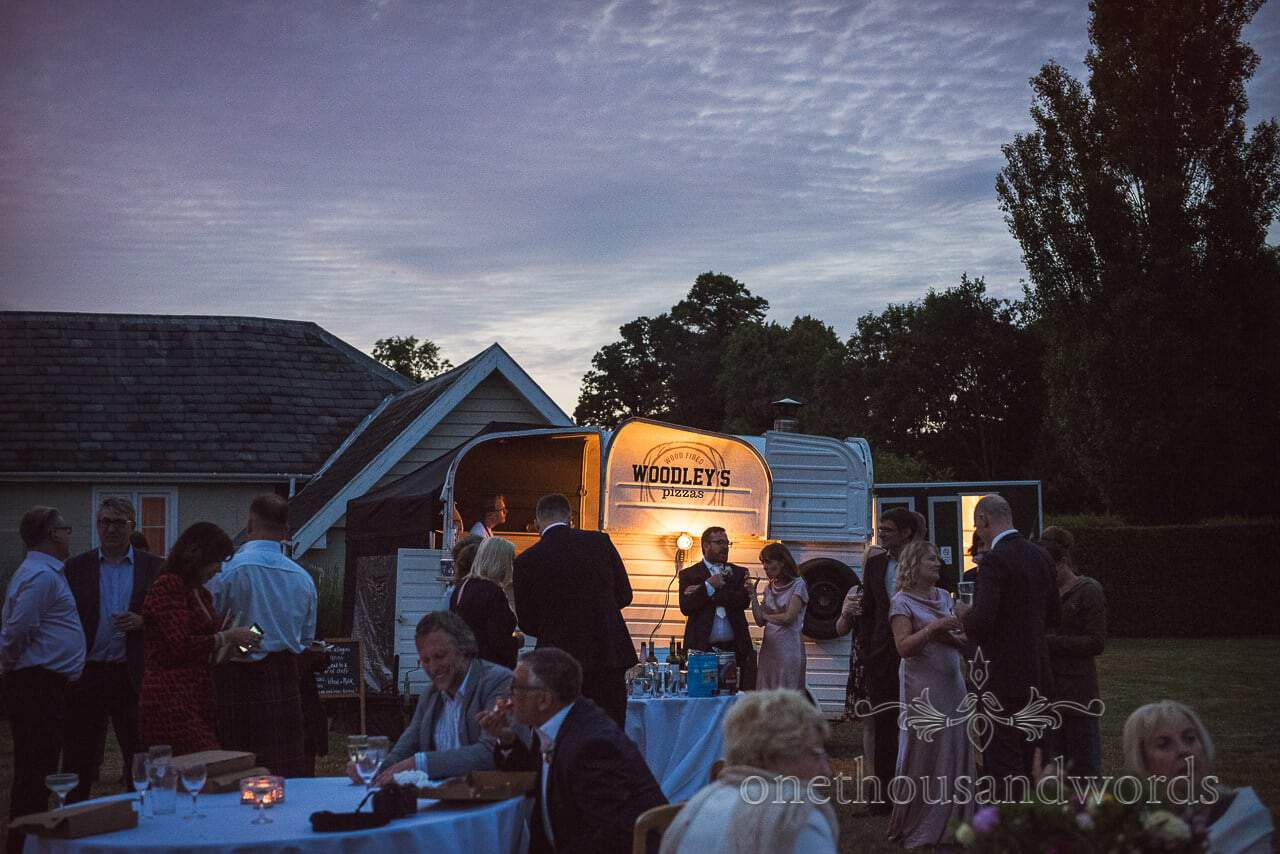 Guests enjoy drink and pizza at Countryside Manor House Wedding