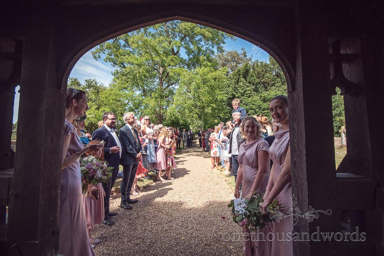 Guests line the church path armed with confetti from countryside wedding