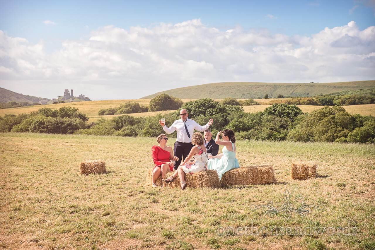 Guests relax in field overlooked by Corfe castle at Purbeck Valley Farm Wedding