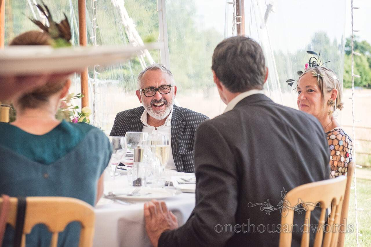 Guests share a joke during marquee reception at countryside wedding