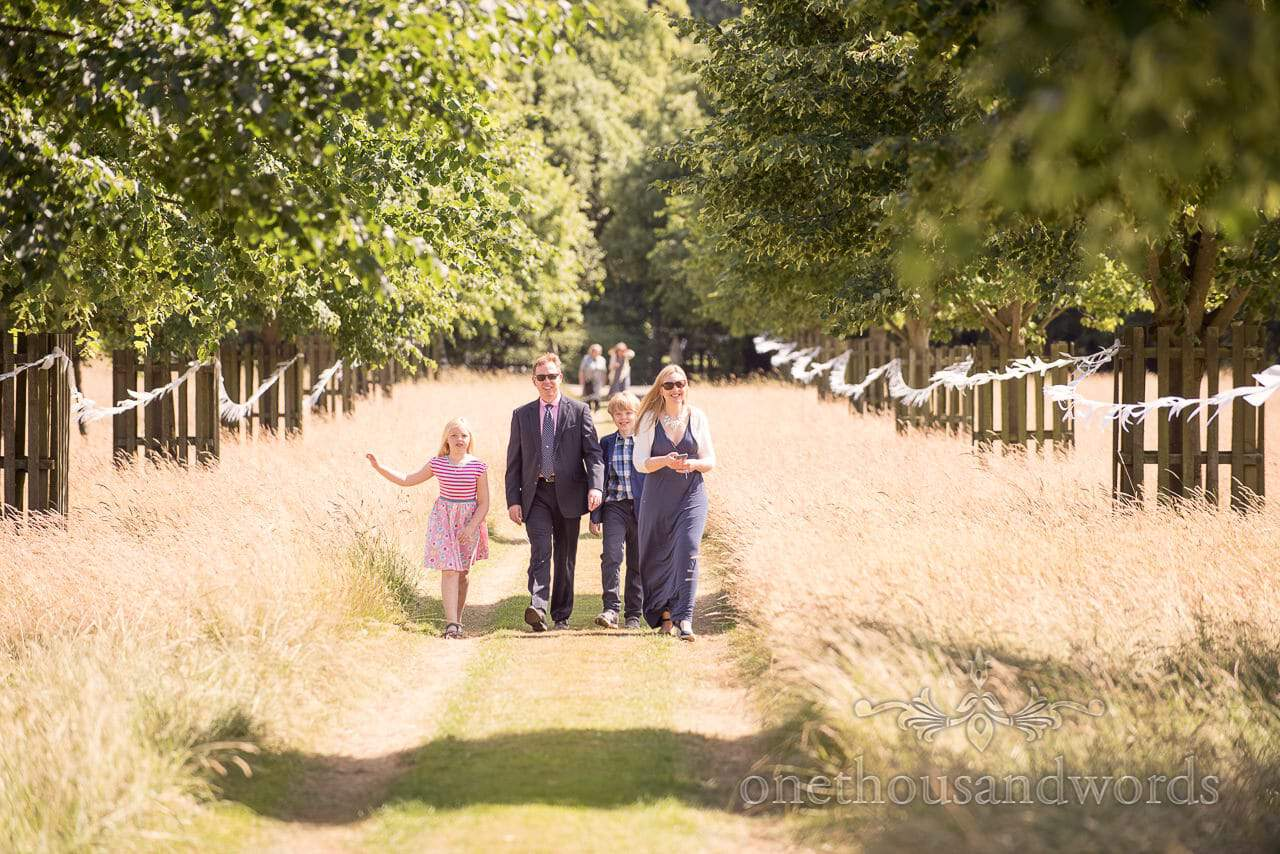 Guests walk up driveway to reception at countryside wedding