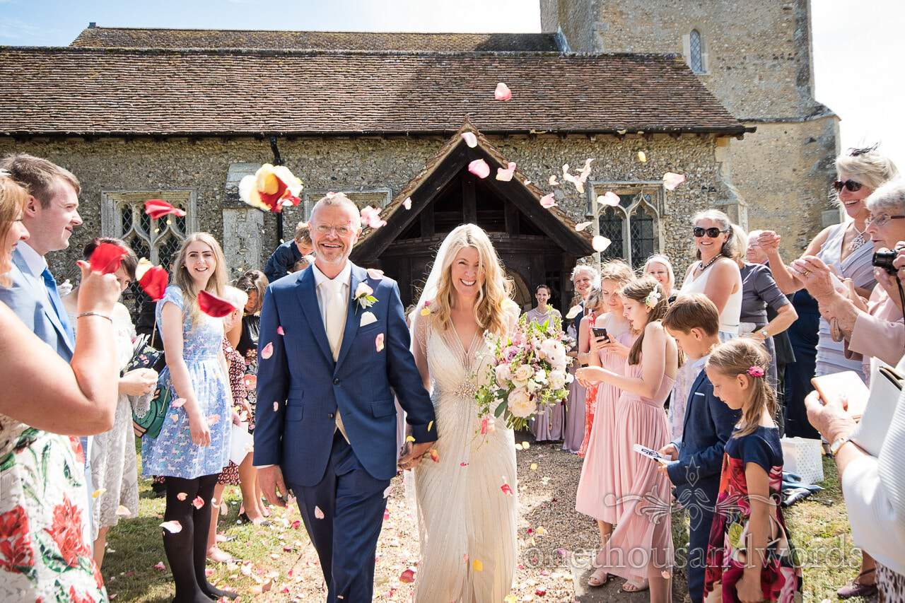 Newlyweds are showered with confetti from countryside wedding