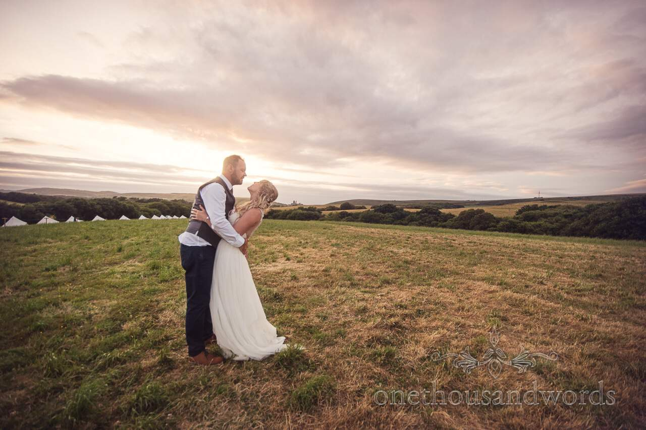 Newlyweds embrace in field at Purbeck Valley Farm Wedding Photographs