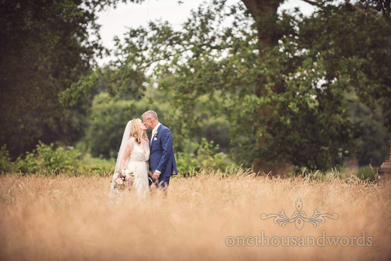 Newlyweds kiss in grassy field from Countryside Manor House Wedding