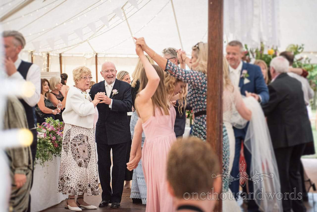 Packed dance floor during marquee reception at countryside wedding