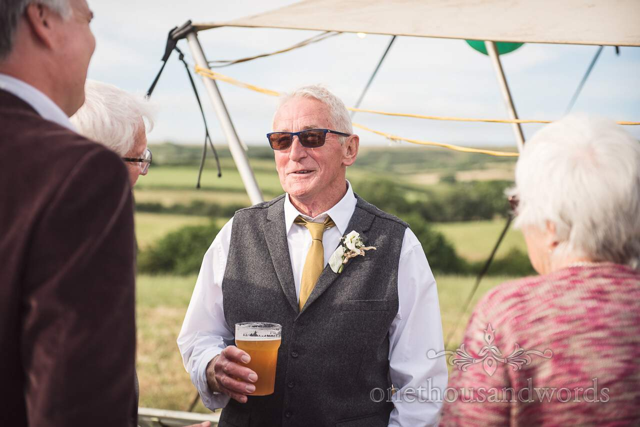 Purbeck Valley Farm Wedding Photographs of father of the bride relaxing with a pint