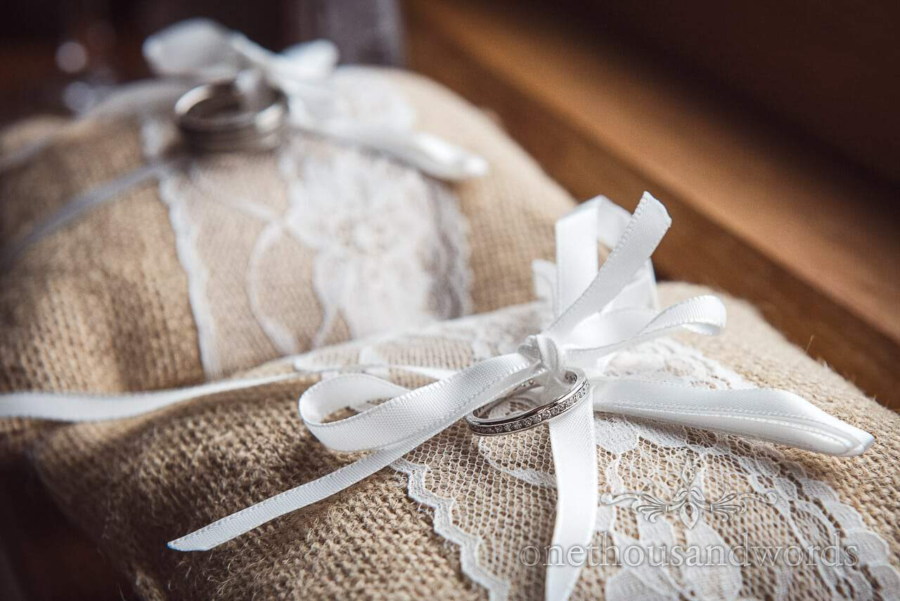 Purbeck Valley Farm Wedding Photographs of wedding rings on lace detailed pillows