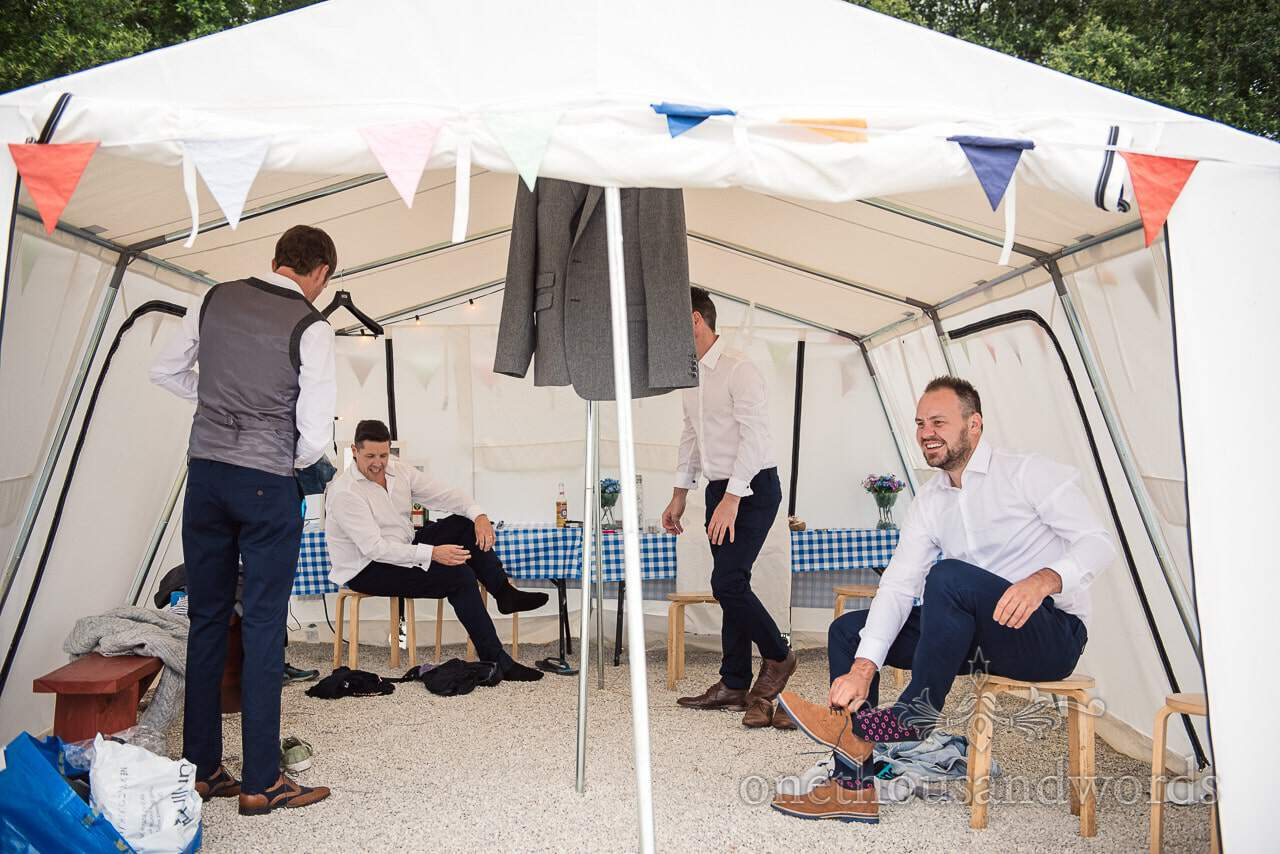 Purbeck Valley Farm Wedding Photographs of groom and groomsmen getting ready in mess tent