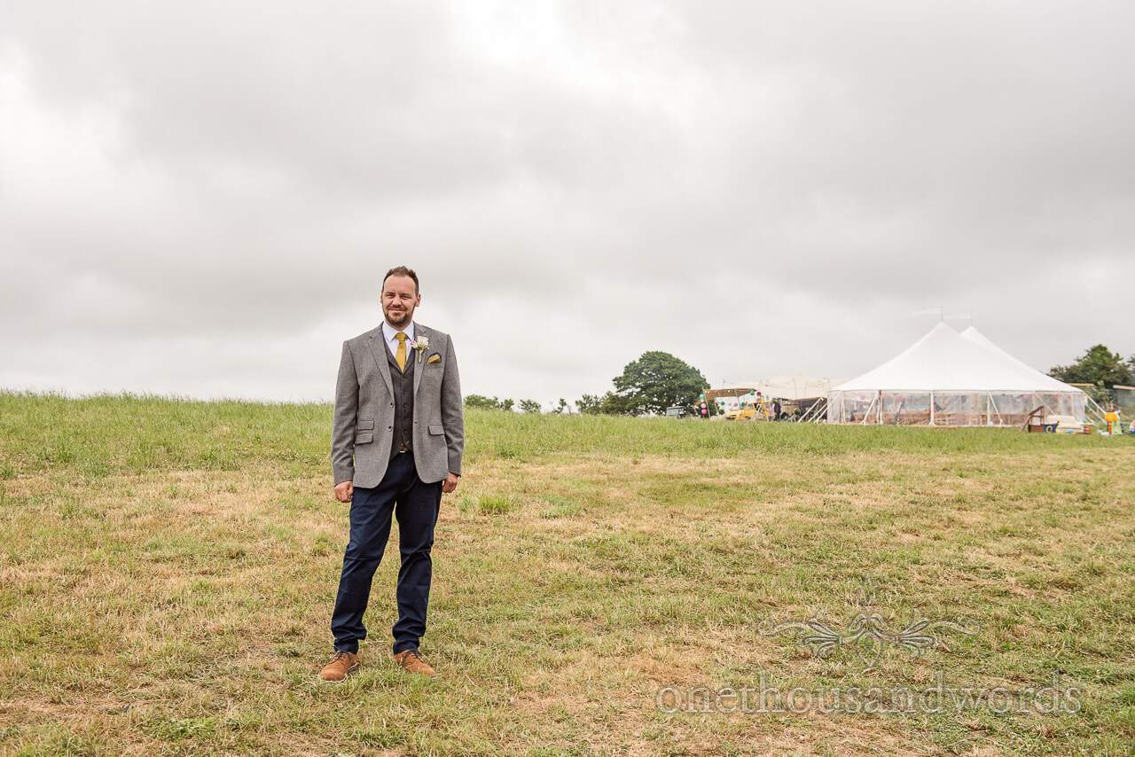 Purbeck Valley Farm Wedding Photographs of groom in field before farmhouse ceremony
