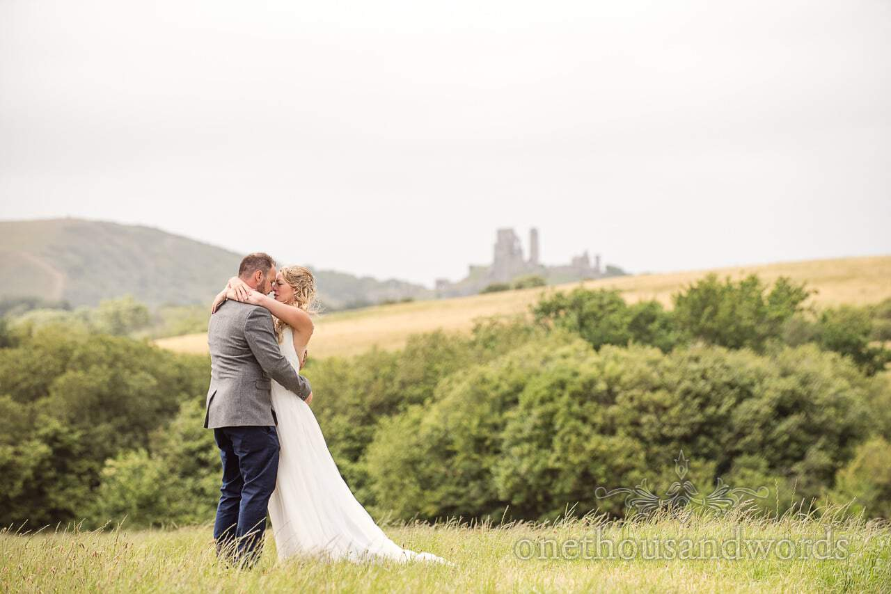 Purbeck Valley Farm Wedding Photographs of newlyweds embrace in grassy field