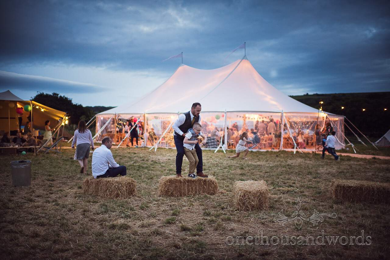 Sailcloth marquee lit up against evening sky from Purbeck Valley Farm Wedding Photographs