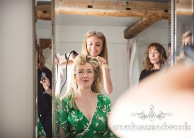 Smiling bride has hair styled on morning of countryside wedding