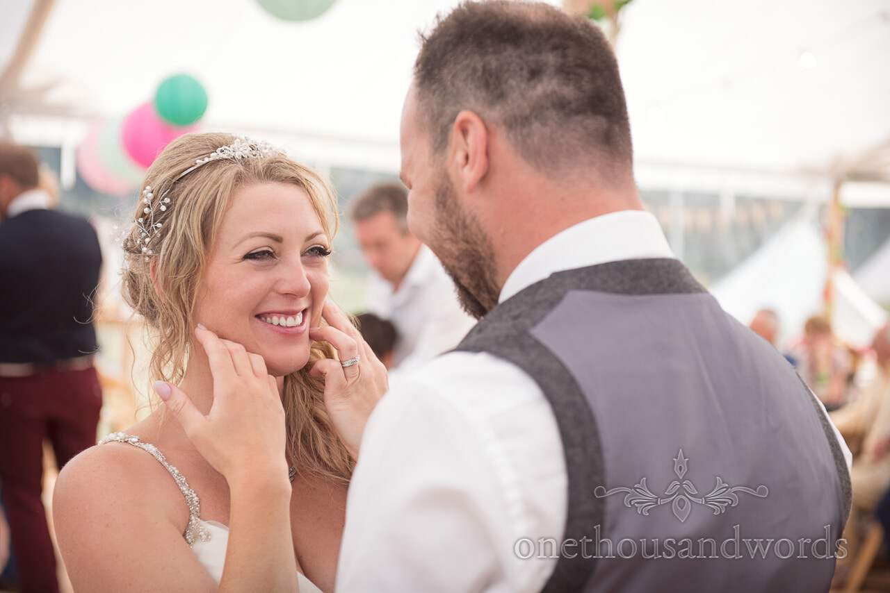 Smiling bride looks at her husband from Purbeck Valley Farm Wedding Photographs