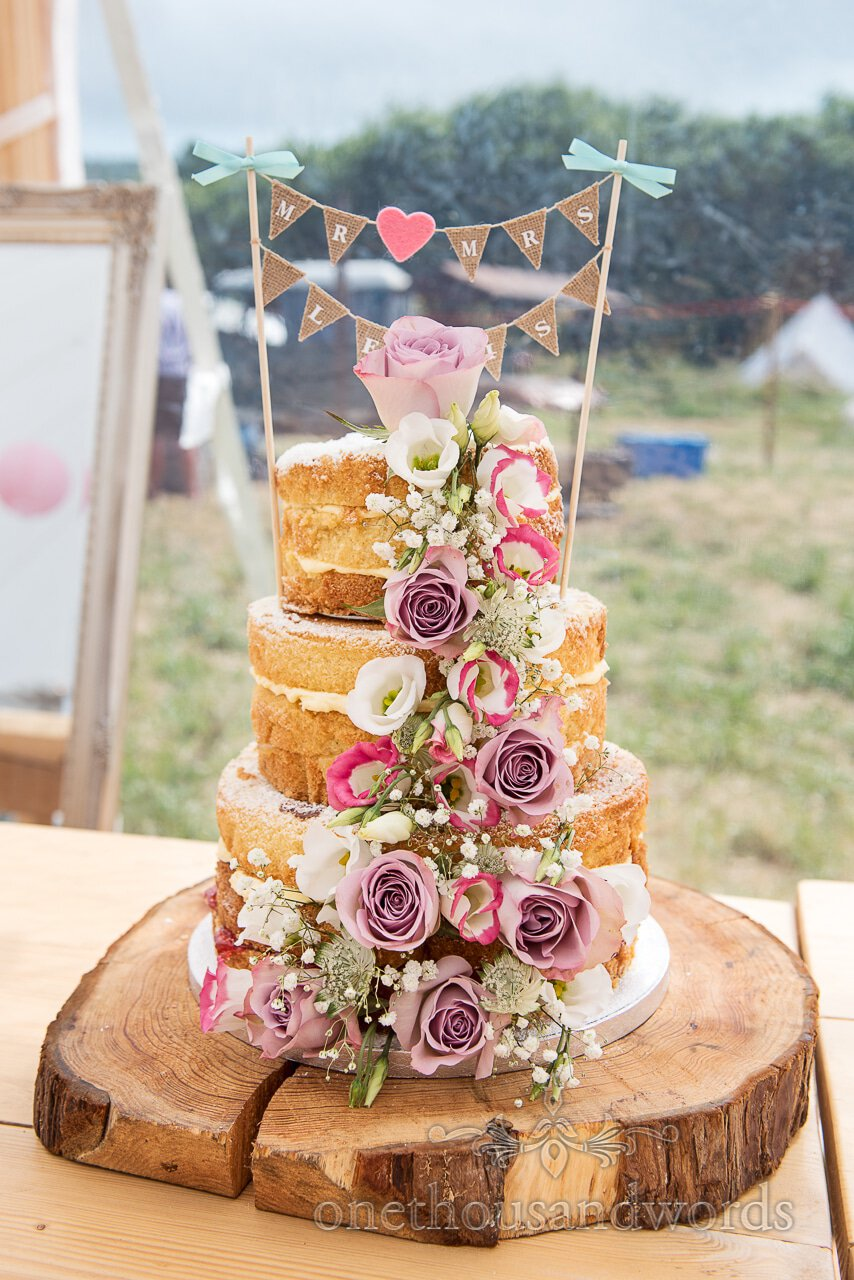 Three tiered wedding cake decorated with flowers at Farm wedding reception