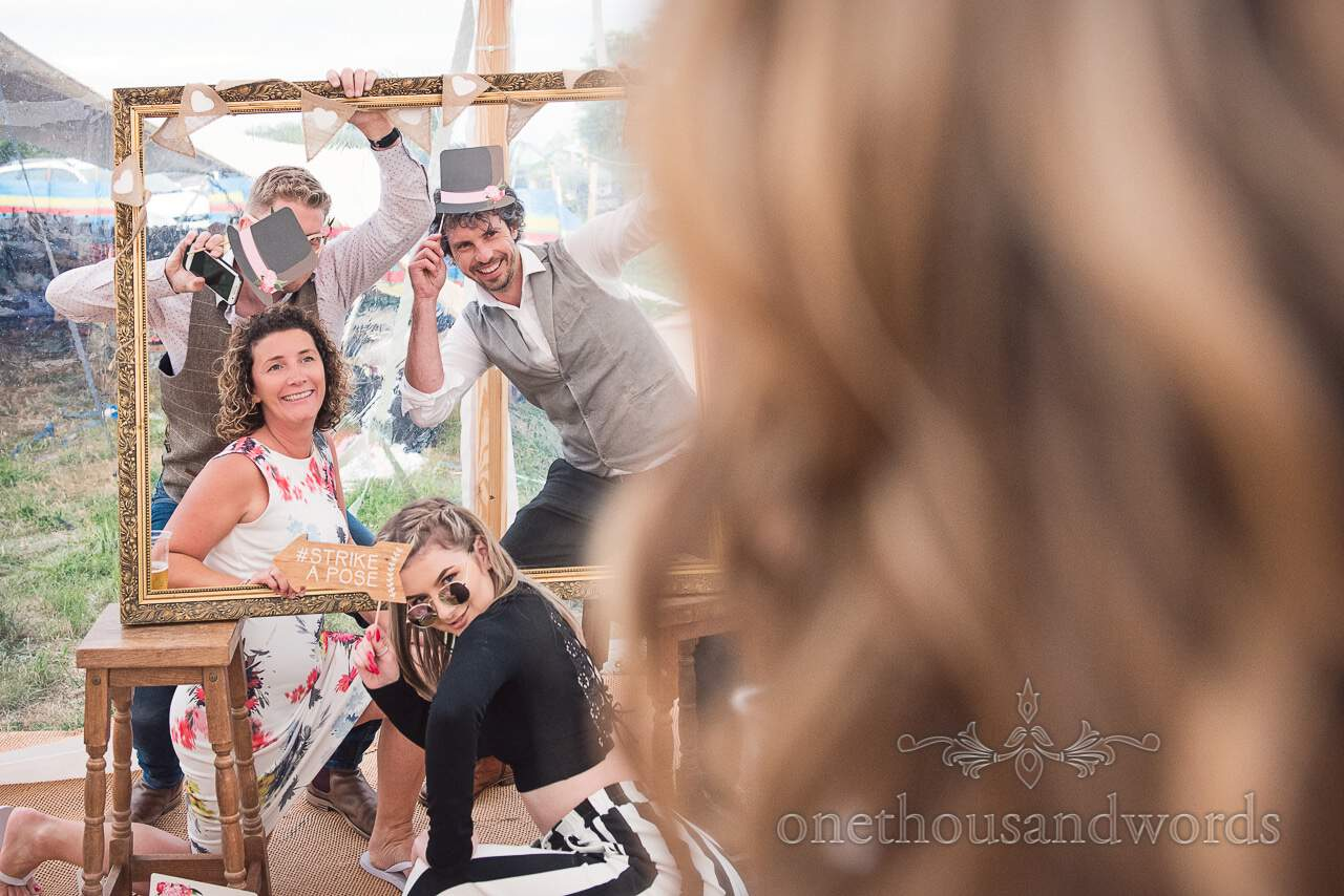 Wedding guests use the photo frame and props at Purbeck Valley Farm Wedding Photographs