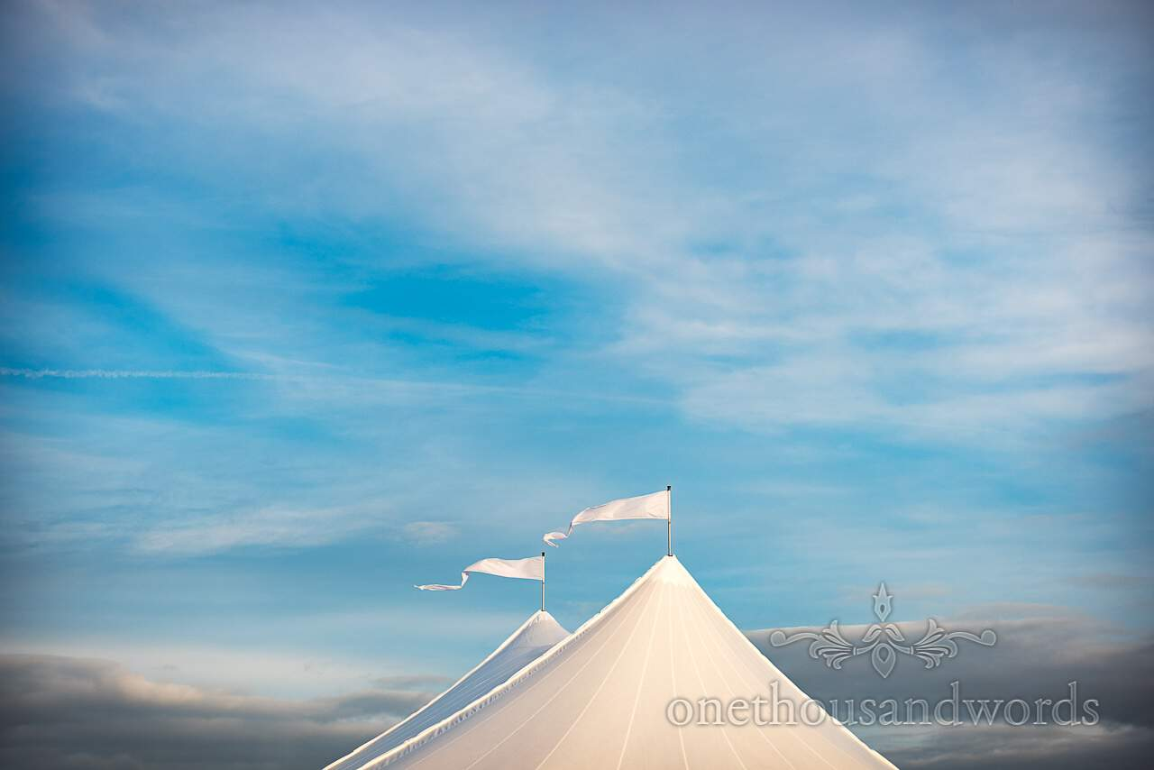 White flags atop Sailcloth marquee from Purbeck Valley Farm Wedding Photographs