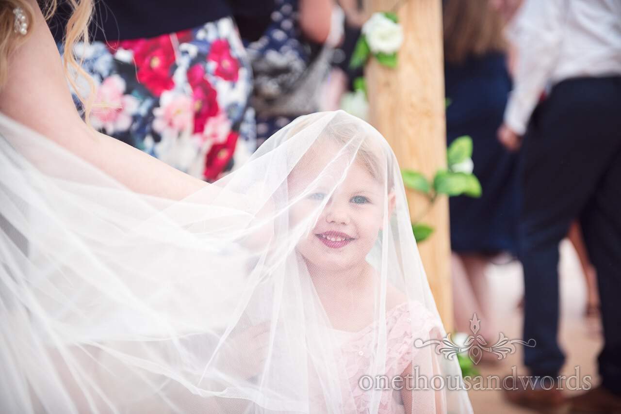 Young wedding guest under wedding dress from Purbeck Valley Farm Wedding