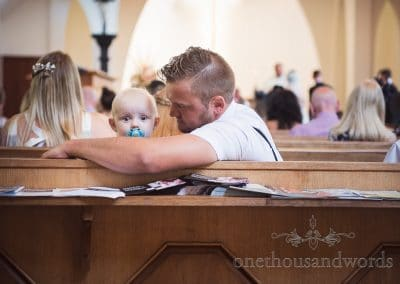 Baby looks over the back of the church pew at Sandbanks Church Wedding