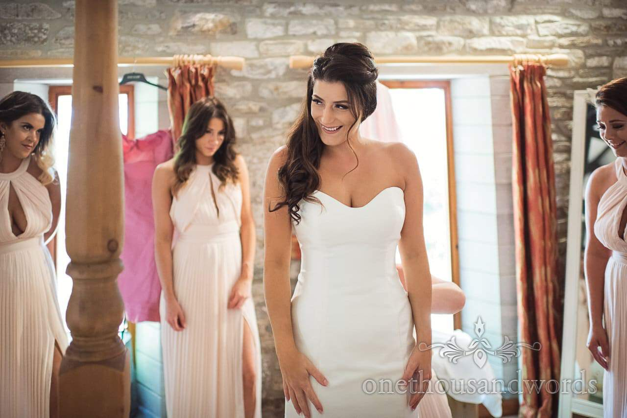 Beautiful bride puts on wedding dress watched by bridesmaids on wedding morning