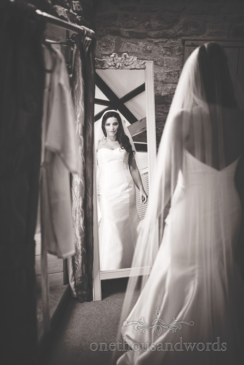 Black and white wedding photo of stunning bride in mirror on wedding morning