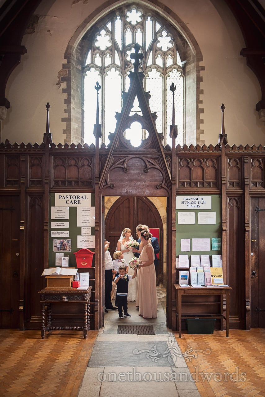Bride and bridesmaids wait in ornate wooden church entrance before wedding