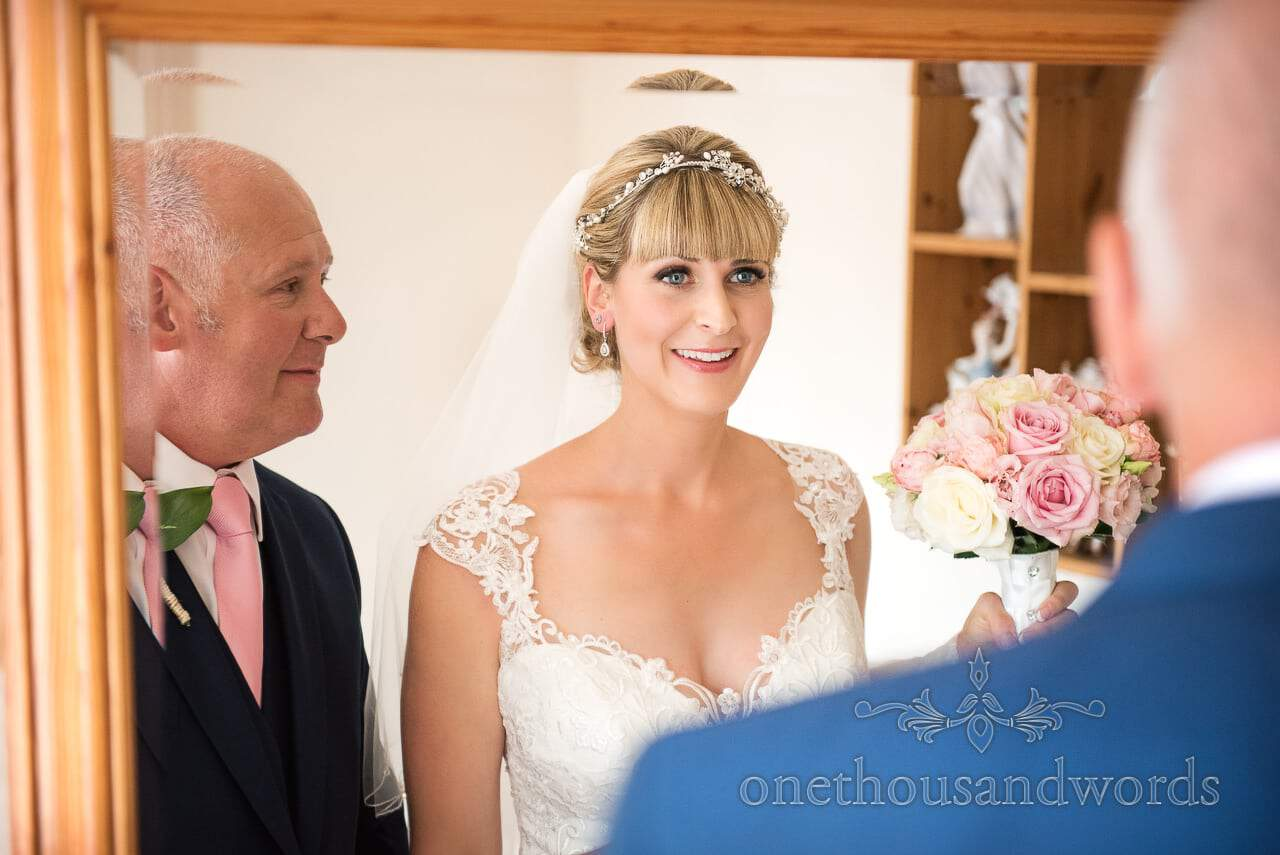 Bride and father look into a framed mirror before leaving for wedding ceremony
