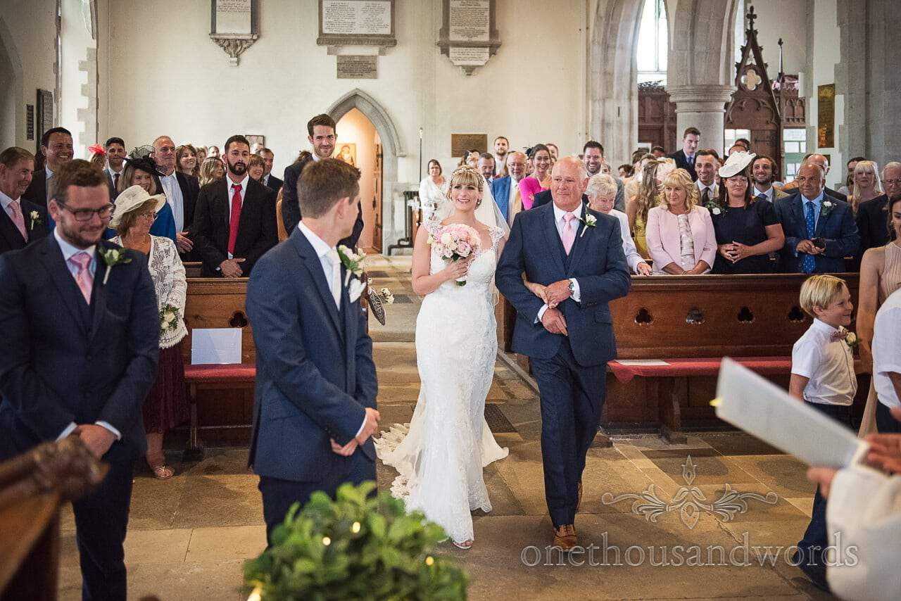 Bride and father walk up church aisle watched by groom and wedding guests